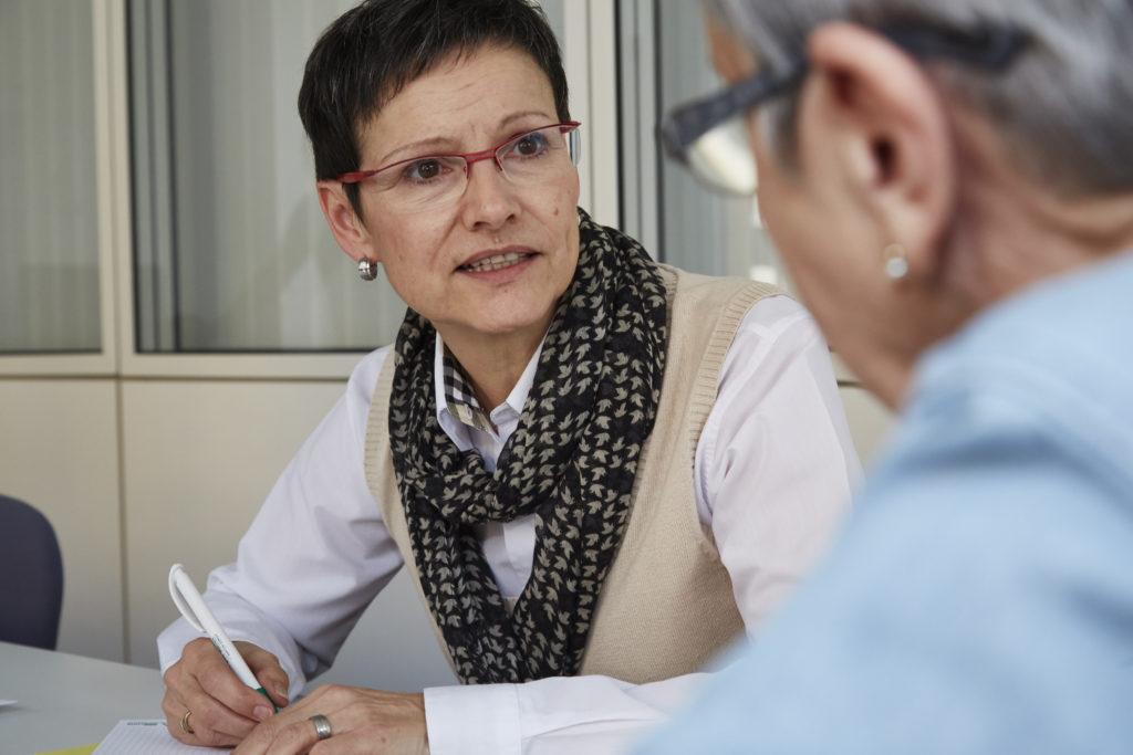 seniorin mit schwarzem kurzhaarschnitt und roter brille in sozialberatung