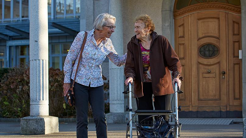 links aeltere Frau mit weissem Kurzhaarschnitt und bunter Bluse und dunklen Hosen rechts betreute Dame mit brauner Jacke und Rollator lachen einander an