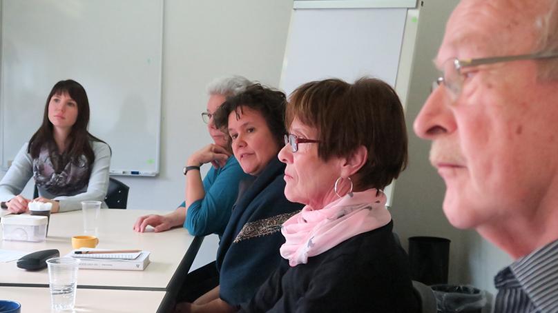 gruppe von angehörigen im seminarraum mit flipchart