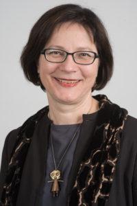 Portrait Frau mittleren Alters kurze dunkle Haare Brille laechelnd