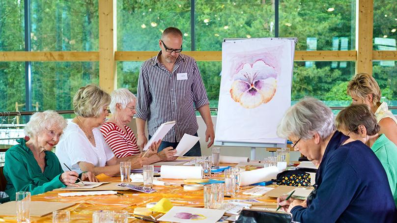 Mann unterrichtet einer Gruppe von Seniorinnen Malen