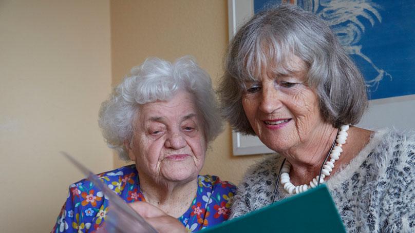 zwei seniorinnen schauen unterlagen an