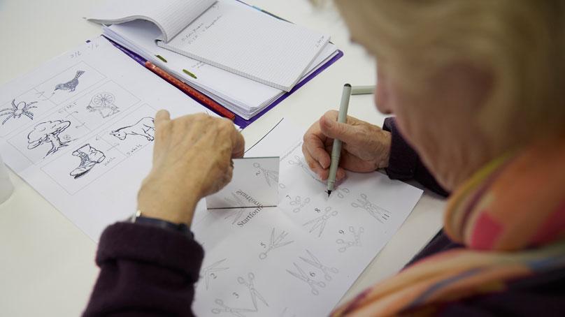 Seniorin mit Stift und Aufgaben zu Gedaechtnistraining