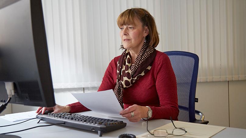 seniorin in rotem pullover berechnet ergaenzungsleistungen