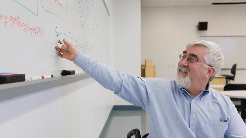 älterer Mann mit Bart und Brille erklaert etwas am whiteboard