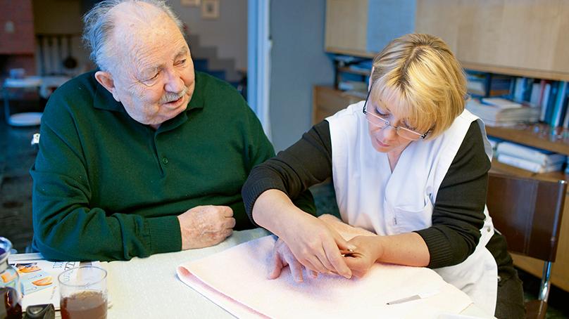 Pflegerin schneidet älterem Mann die Fingernaegel