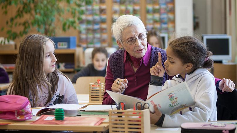 Seniorin hilft zwei Schülerinnen im Schulzimmer
