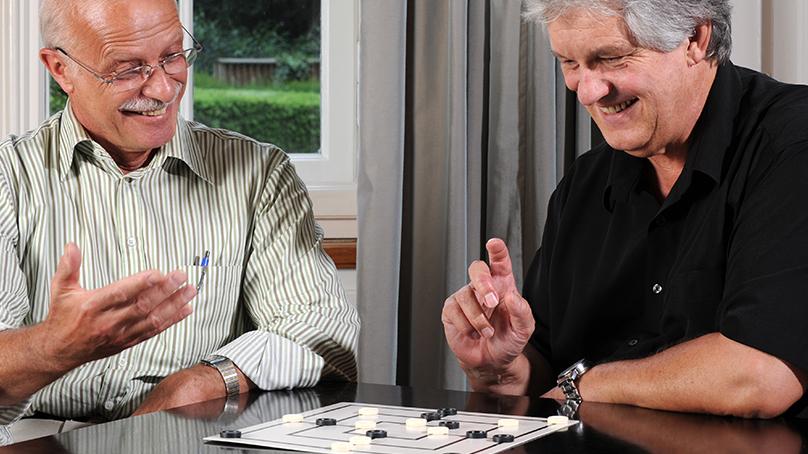 gesellschafts spiel senior mit brille und senior mit schwarzem hemd