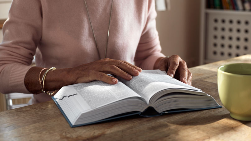 Teilbild Frau lesend am Tisch