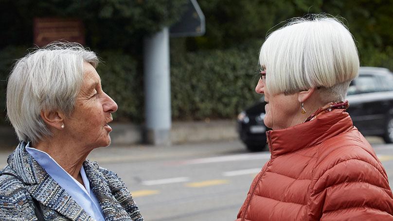 zwei Seniorinnen im Gespraech auf der Strasse Seitenansicht