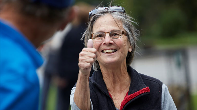 freiwillige seniorin mit kurzhaarschnitt und brille