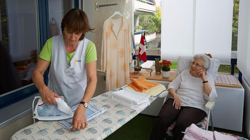 Haushalthilfe bügelt Handtuch für Seniorin