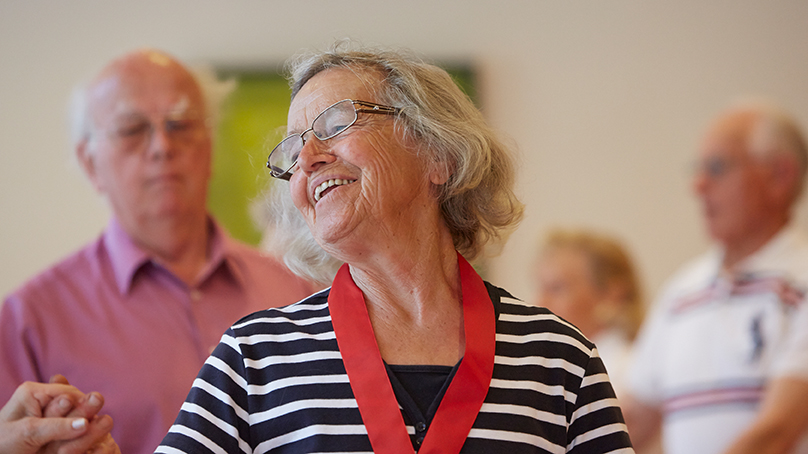 seniorin mit brille und gestreiftem oberteil beim senioren tanz