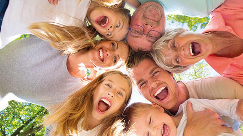 Zwei Frauen und zwei Männer sowie 3 Mädchen stehen im Kreis und halten lachend die Köpfe zusammen