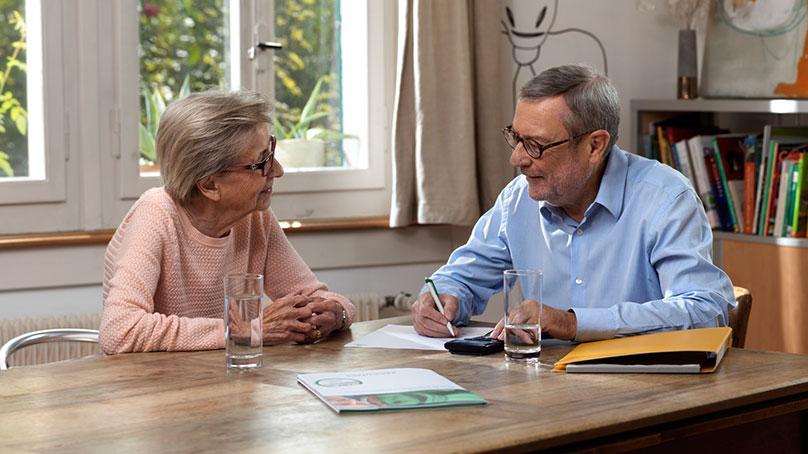 senior in blauem hemd und seniorin mit rosa pullover bei büroassistenz