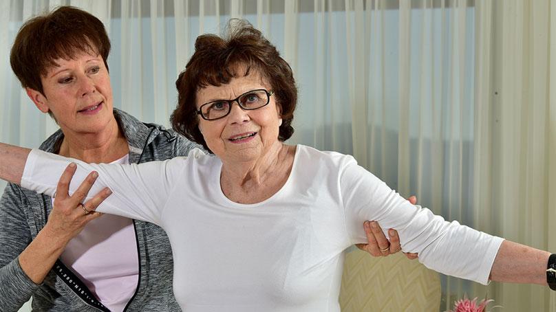 Sportleiterin mit Seniorin beim dehnen