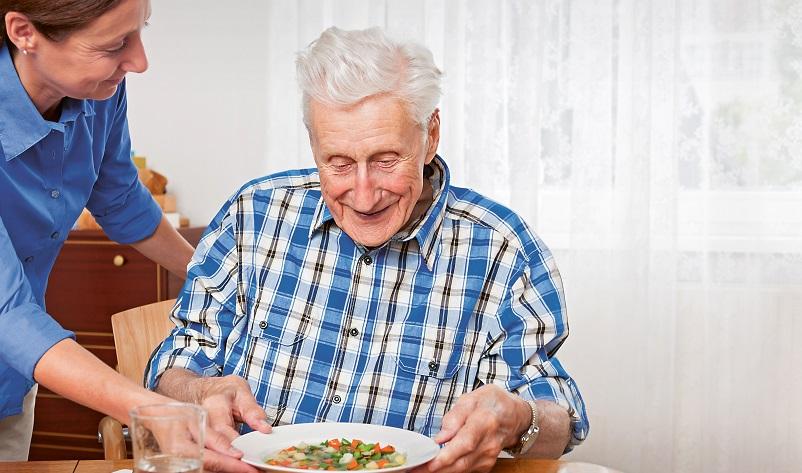 Pflegerin gibt Mahlzeit an Senior