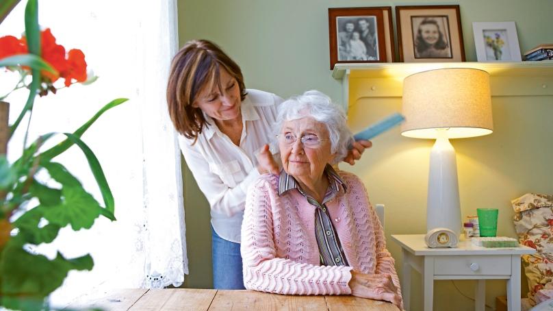 Pflegerin kämmt Seniorin die Haare