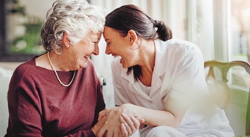 Seniorin und Pflegerin halten sich die Hände und lachen