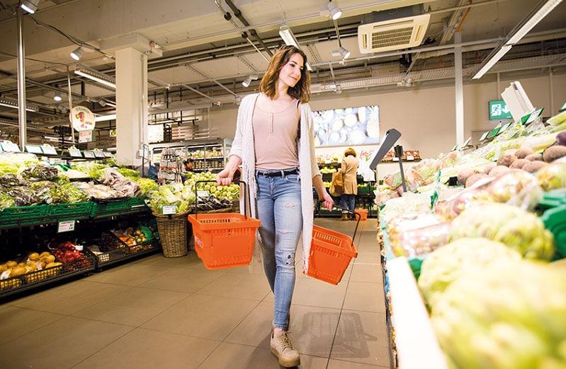 Junge Frau mit zwei Migros Einkaufskörben in Obst- und Gemüseabteilung