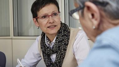 Frau mit schwarzem Kurzhaarschnitt und Kugelschreiber in der Hand in Beratung mit Seniorin mit Brille und hellblauer Bluse verschwommen
