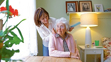 Frau kämmt älterer Dame die Haare