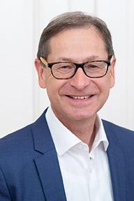 Portrait Mann mittleren Alters laechelnd mit Brille