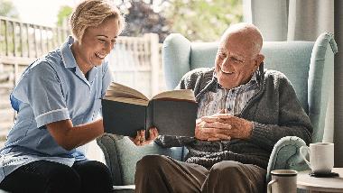 Seniorenbetreuerin liest älterem Mann ein Buch vor, der im Stuhl sitzt