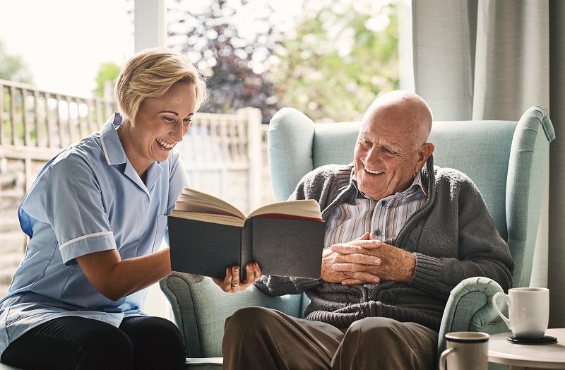 Seniorenbetreuerin liest älterem Mann ein Buch vor