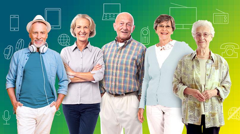 fuenf ältere Menschen lachend vor Wand mit Symbolen verschiedener Medien