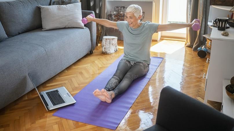 Seniorin trainiert im Sitzen mit Hanteln vor ihrem Computer