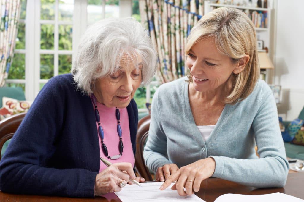 Junge Frau hilft Seniorin ein Formular auszufüllen