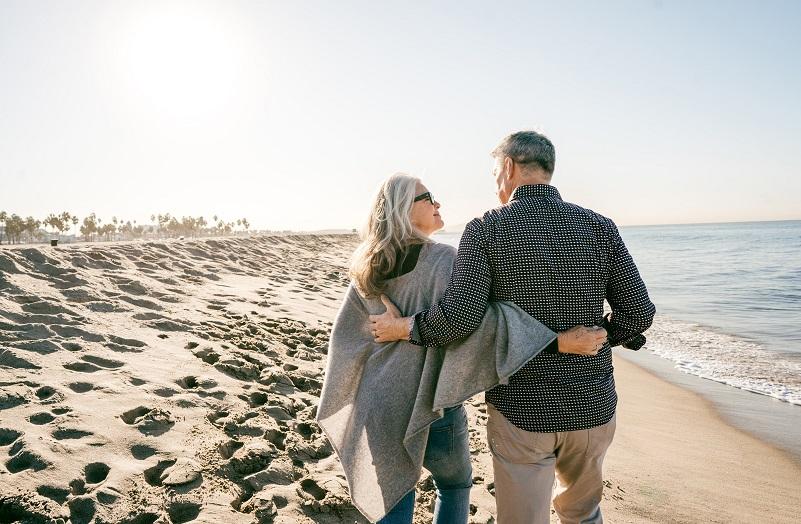 zwei Senioren gehen am Strand spazieren